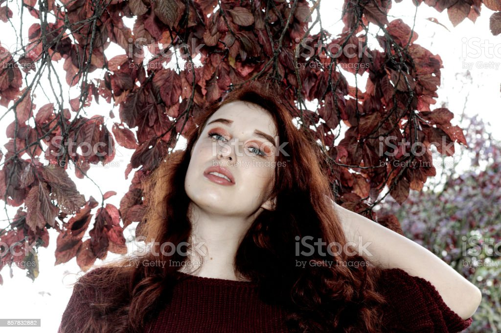 Autumn outdoor girl redhead with purple leaves of Myrobalan plum tree stock photo