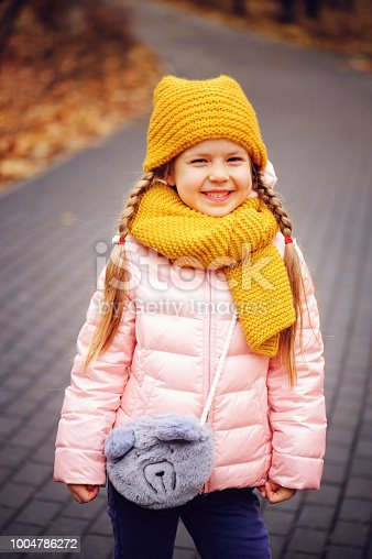 istock autumn outdoor portrait of happy little child girl enjoying the walk in sunny park in warm knitted hat and scarf 1004786272