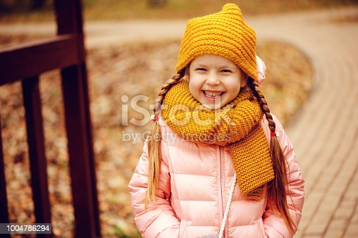 istock autumn outdoor portrait of happy little child girl enjoying the walk in sunny park in warm knitted hat and scarf 1004786294