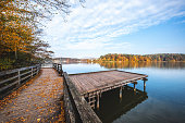 Idyllic autumn scene with wooden jetty by the lake.
