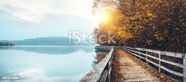 Wooden path by the misty lake. Early morning view with sun shinning through the fog.