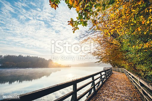 Colorful autumn path by the lake at sunrise.