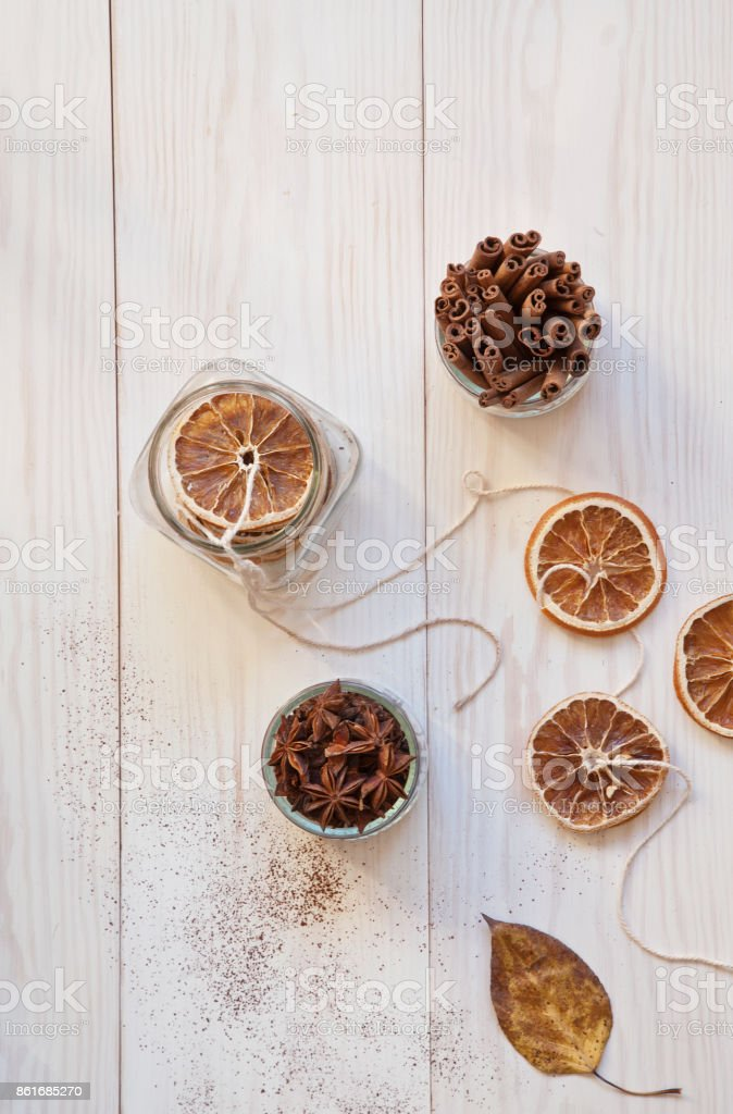 Autumn pattern of leaves and dried orange slices on a white wooden background. stock photo