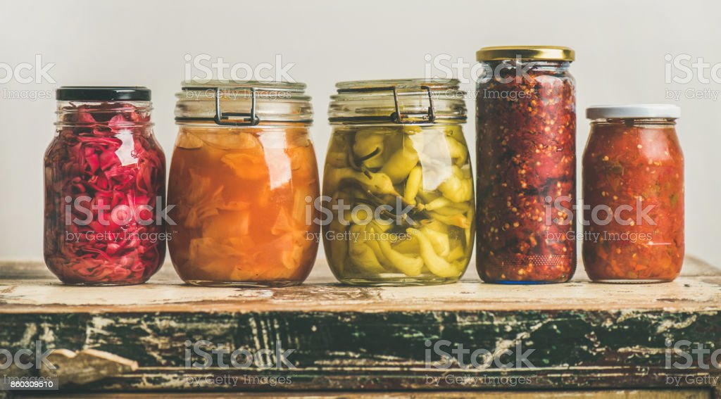 Autumn pickled colorful vegetables in jars placed in line stock photo