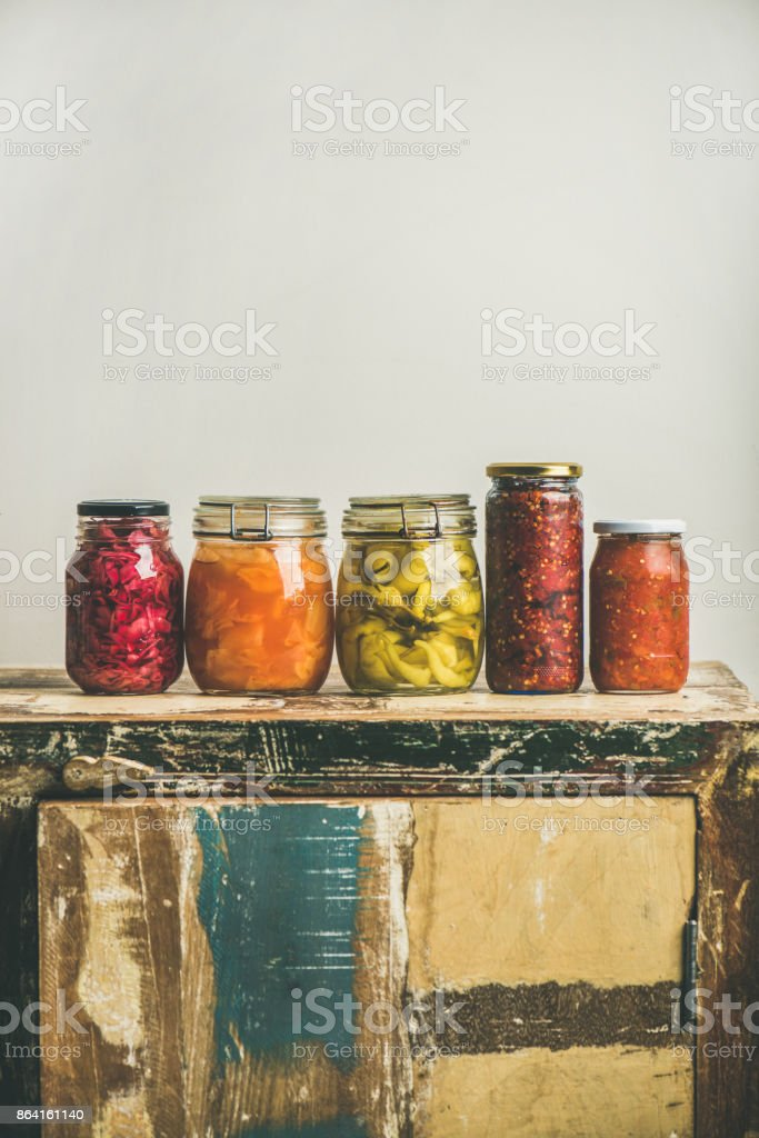Autumn pickled vegetables in jars placed in line, copy space royalty-free stock photo