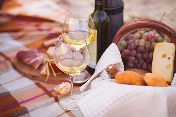 autumn picnic by the sea with wine, grapes, bread, cheese - französische land tisch stock-fotos und bilder