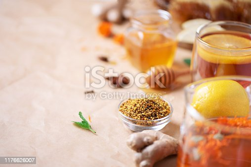 istock Autumn picnic. Herbal tea, honey and bee products, apple, lemon, calendula, spices on craft paper background. Immune system support with alternative medicine. Copy space 1176626007