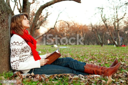 young adult girl sitting in autumn park with a book