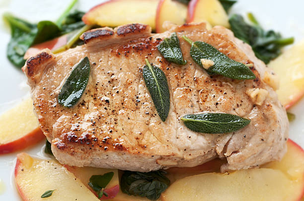 Autumn pork chop dish over sliced apple and spinach stock photo