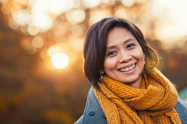 Autumn portrait of a woman A smiling woman in her 40s outdoors in autumn, with sunlight behind her. filipino ethnicity stock pictures, royalty-free photos & images