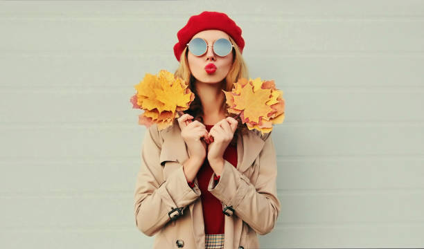 Autumn portrait of beautiful woman with yellow maple leaves, female model blowing red lips sending sweet air kiss wearing french beret over gray background stock photo