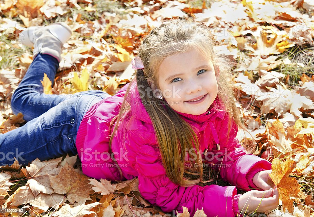 Autumn portrait of cute little girl lying in maple leaves royalty-free stock photo
