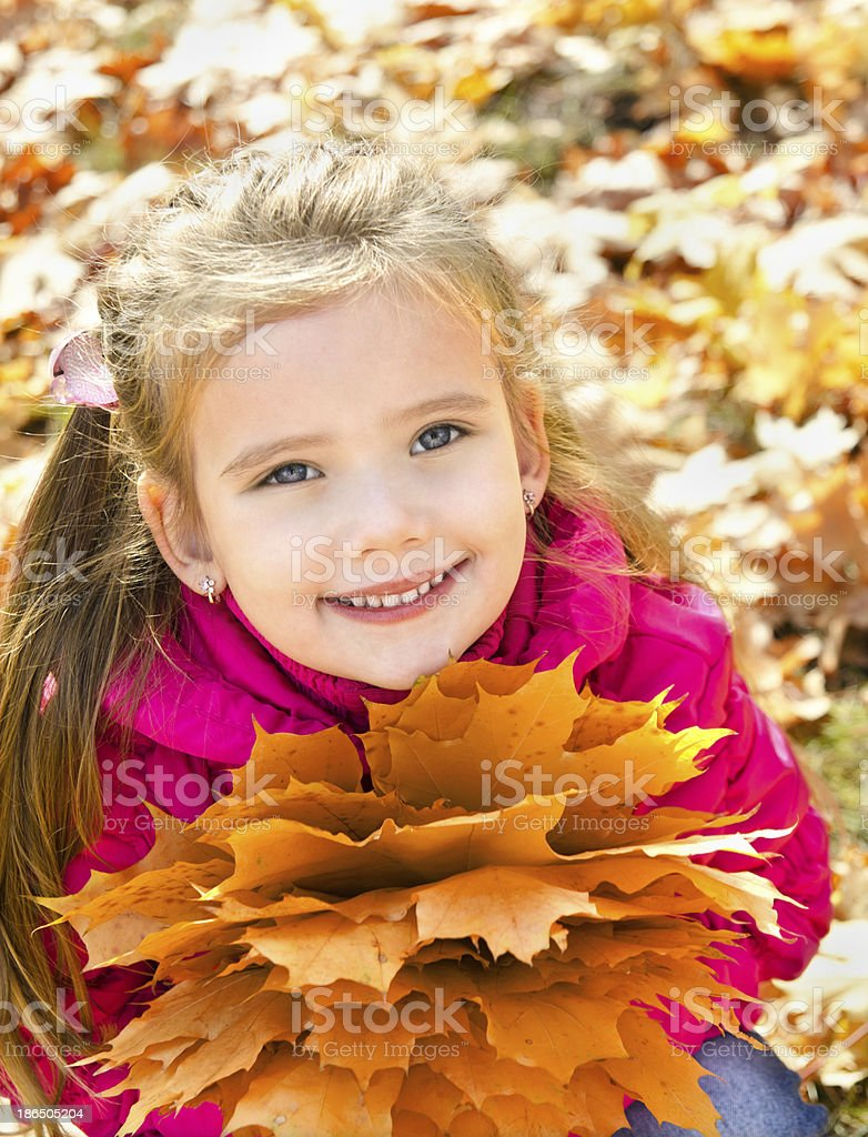 Autumn portrait of cute smiling little girl with maple leaves royalty-free stock photo