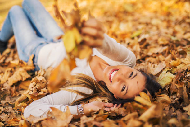 Autumn portrait of girl Woman laying down on the pile of leafs and playing beautiful woman stock pictures, royalty-free photos & images