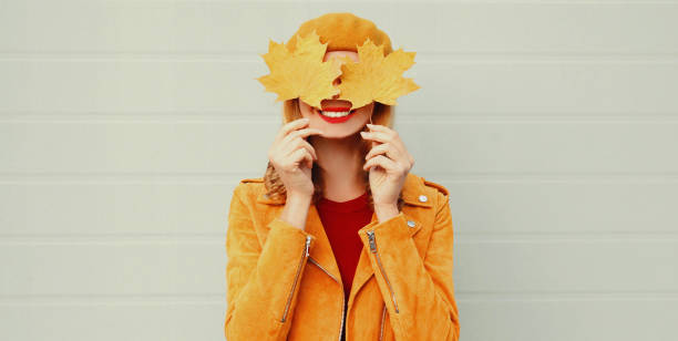 Autumn portrait of happy smiling woman covering her eyes with yellow maple leaves over gray background stock photo