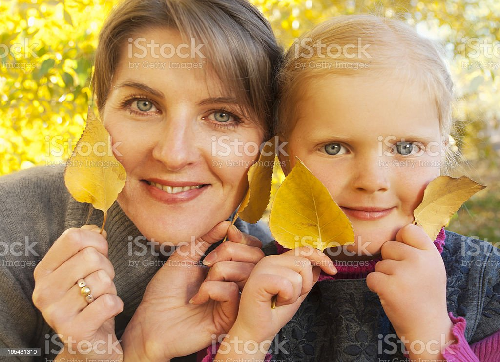 Autumn portrait of mother and daughter with yellow leaves royalty-free stock photo