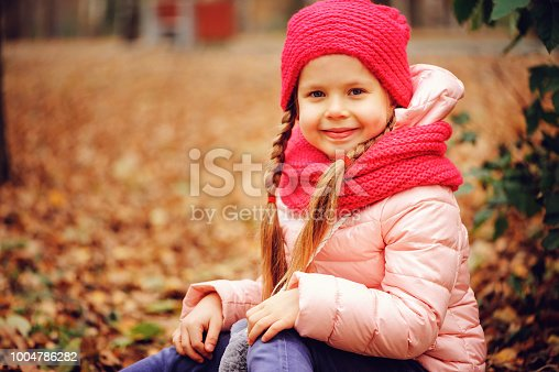 istock autumn portrait of smiling child girl enjoying the walk in sunny park in warm knitted hat and scarf 1004786282