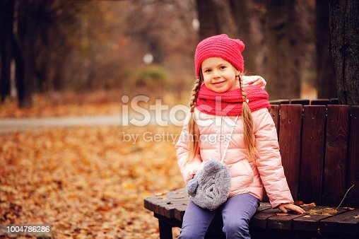 istock autumn portrait of smiling child girl sitting on bench in park in warm knitted hat and scarf, enjoying outdoor walk in sunny day 1004786286
