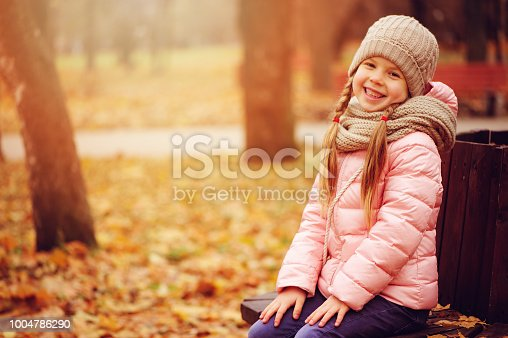 istock autumn portrait of smiling child girl sitting on bench in park in warm knitted hat and scarf, enjoying outdoor walk in sunny day 1004786290
