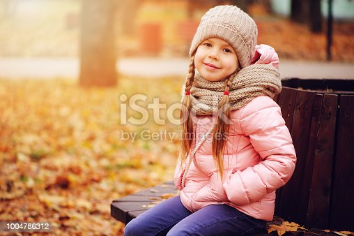 istock autumn portrait of smiling child girl sitting on bench in park in warm knitted hat and scarf, enjoying outdoor walk in sunny day 1004786312
