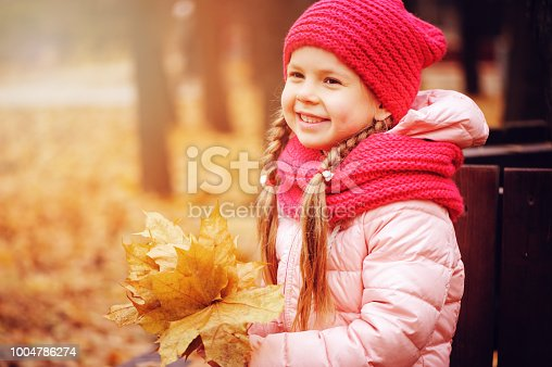 istock autumn portrait of smiling child girl with bouquet of leaves, sitting on bench in park in warm knitted hat and scarf, enjoying outdoor walk in sunny day 1004786274