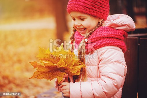 istock autumn portrait of smiling child girl with bouquet of leaves, sitting on bench in park in warm knitted hat and scarf, enjoying outdoor walk in sunny day 1004786298