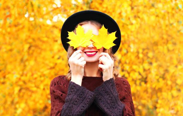 Herbst Porträt lächelnde Frau versteckt ihre Augen, die gelb mit schwarzen Hut Ahornblätter – Foto