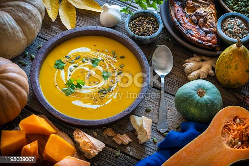 Autumn pumpkin soup and ingredients on rustic wooden table