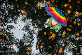 Little boy standing in the water puddle on the rainy day with colorful umbrella and looking up.