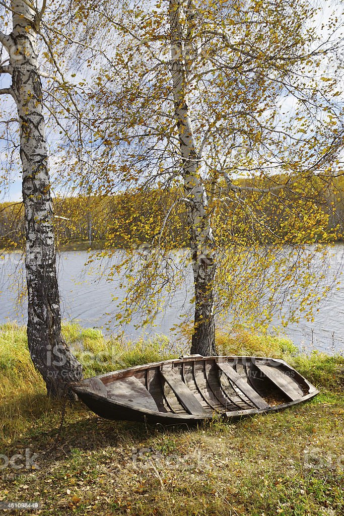 Autumn riverbank with old boat royalty-free stock photo