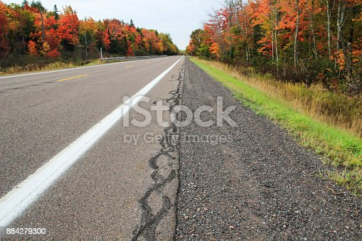 istock Autumn Road Trip Background In Michigan Upper Peninsula With Blacktop Road And Diminishing Perspective 884279300