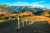 Picturesque colorful autumn countryside landscape with rural wooden huts and high mountains in background, Bran, Transylvania, Romania, Europe