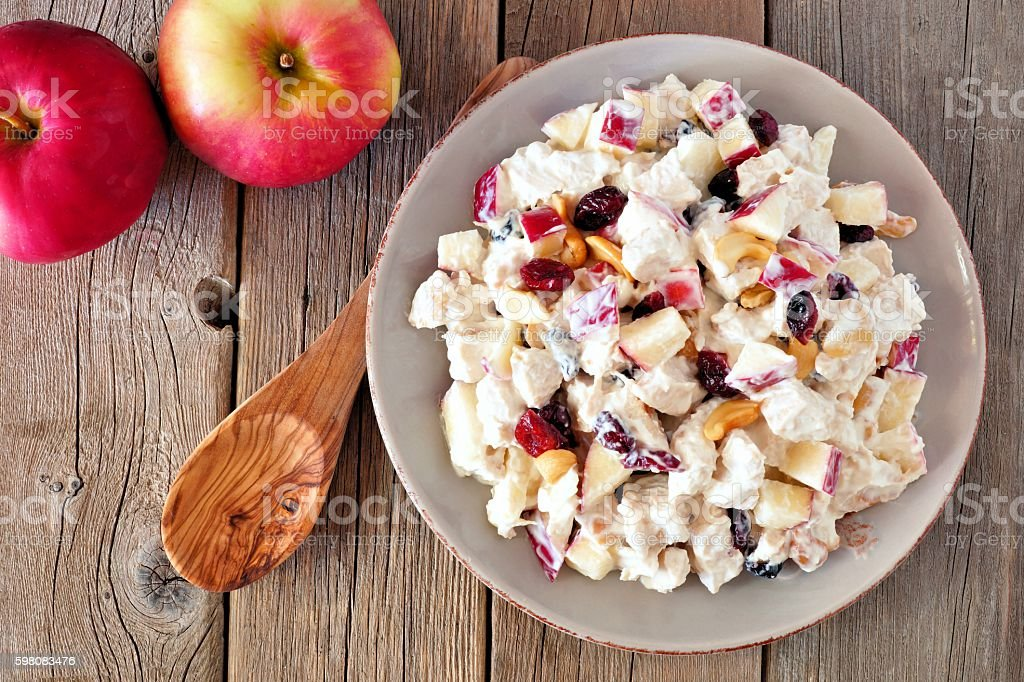 Autumn saladwith chicken, apples, nuts and cranberries, over wood stock photo