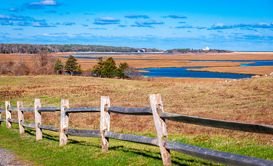 Autumn colors are prevalent in the salt marsh viewed from Fort Hill in Eastham, Massachusetts looking toward the Coast Guard Station on the right.