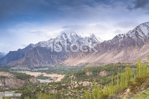 view of the Pakistani Karakorum mountains, K2 and Nanga Parbat. Clouds partly hide mountains, valleys and glaciers.