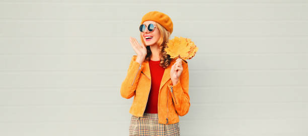 Autumn season! happy surprised woman with yellow maple leaves in french beret posing over gray wall background stock photo