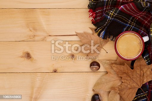 Autumn season; coffee, blanket and fall leaves over rustic wood background