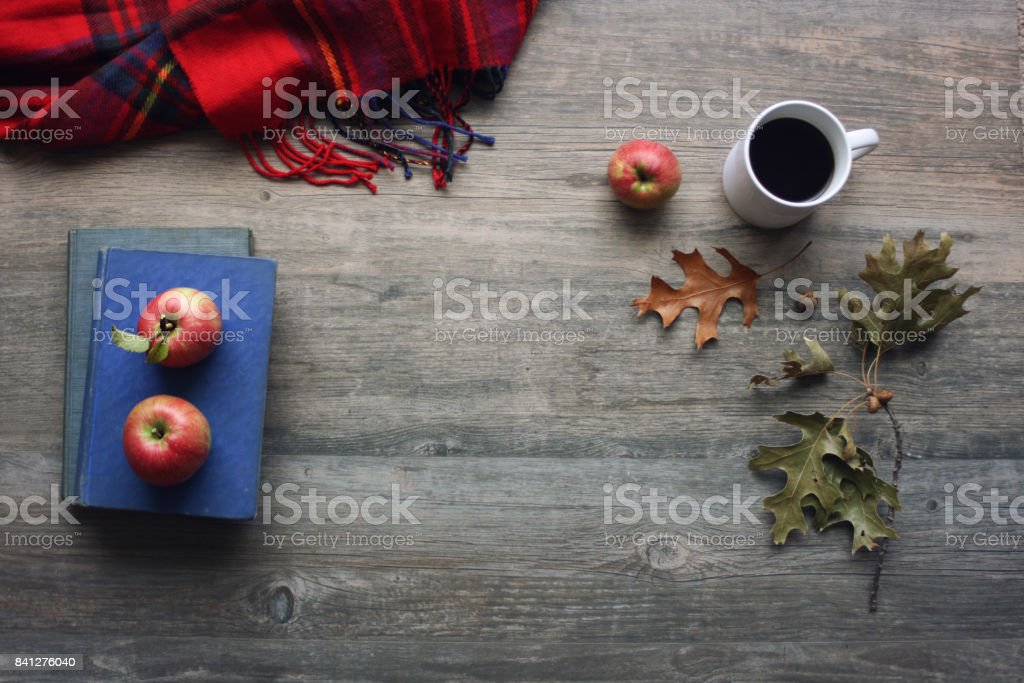 Autumn season still life with red apples, books, red plaid blanket, black coffee cup and fall leaves over rustic wooden background stock photo
