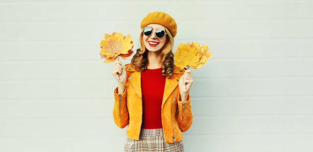 Autumn season! Stylish happy smiling woman with yellow maple leaves in french beret posing over gray wall background stock photo