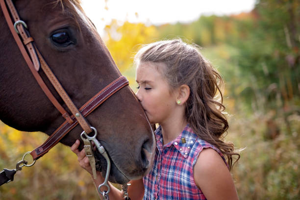 autumn season young girl and horse - kiss стоковые фото и изображения