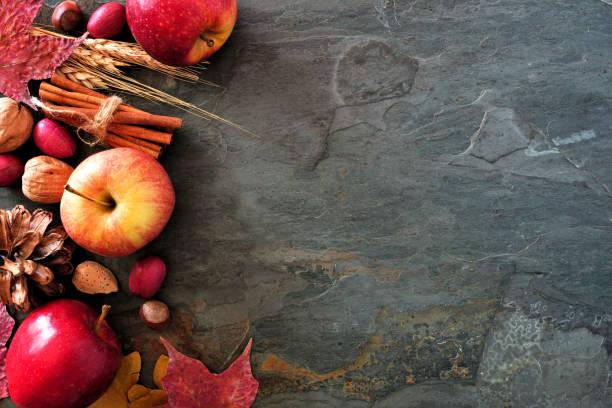 herbst seitenrand äpfel fallen lebensmittel & dekor auf dunklen stein - zimt pekannüsse stock-fotos und bilder