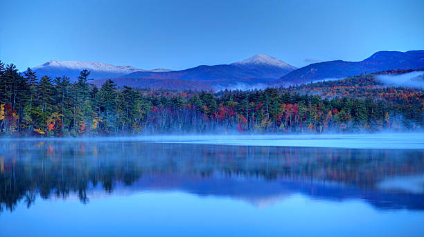 Autumn snowcapped White Mountains in New Hampshire Autumn snowcapped mountains in New Hampshire. Photo taken at dawn on a calm lake during the peak fall foliage season near the White Mountains National Forest. New Hampshire is one of New England's most popular fall foliage destinations bringing out some of  the best foliage in the United States white mountains new hampshire stock pictures, royalty-free photos & images