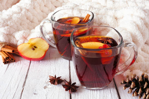 Autumn spiced tea with apples and pomegranates, side view against white wood background with cozy blanket stock photo