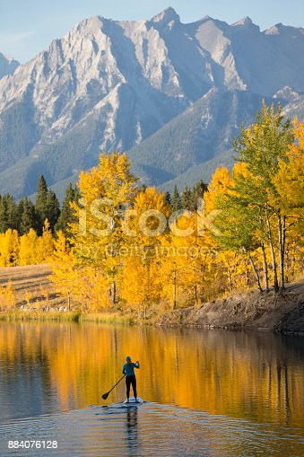 A woman enjoys a end-of-day stand up paddleboard trip on a lake in the Rocky Mountains of Canada in autumn.