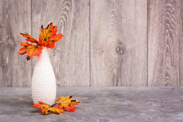 Sonbahar natürmortu. Masada portakal akçaağaç yaprakları olan bir vazo. Beyaz-turuncu-bej renk düzeni stok fotoğrafı