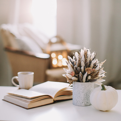 Autumn still life. Coffee cup, flowers, book and pumpkin. Hygge lifestyle, cozy autumn mood. Flat lay, Happy thanksgiving.