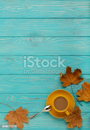 istock Autumn still life - coffee with leaves on a blue wooden background. 846671070