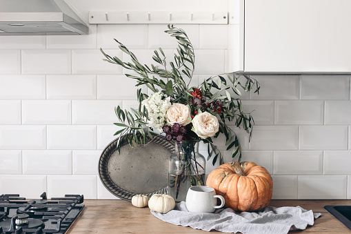 Autumn still life composition in rustic eclectic kitchen interior. Cup of coffee, vintage silver tray and floral bouquet. Wooden table background with pumkins, thanksgiving, Halloween concept.