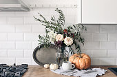 istock Autumn still life composition in rustic eclectic kitchen interior. Cup of coffee, vintage silver tray and floral bouquet. Wooden table background with pumkins. Thanksgiving, Halloween concept. 1272576047