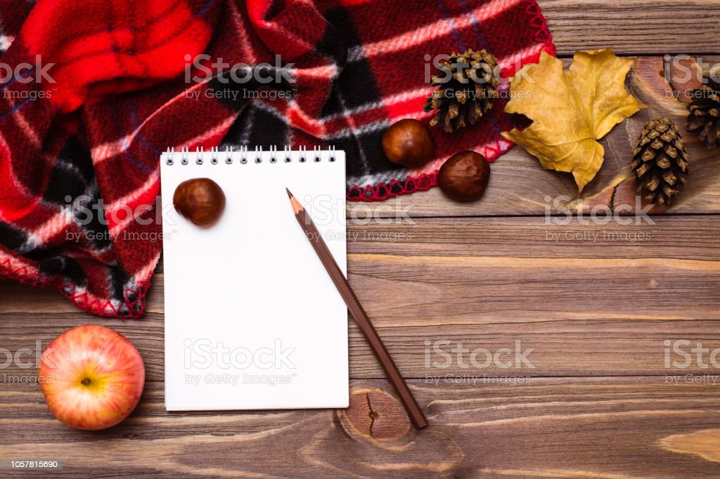 https www istockphoto com photo autumn still life notebook pencil blanket and gifts of autumn on a wooden background gm1057815690 282691377